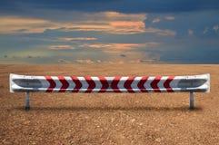 Guardavia dell'acciaio duro sullo sbarco del terreno con il cielo variopinto drammatico Fotografie Stock Libere da Diritti
