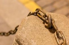 Guarde o suporte de pedra com uma corrente do ferro em uma plaza borrada da pedra do fundo, decoração urbana Fotografia de Stock