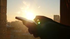 Guarde o telefone em sua mão em um fundo do por do sol, com brilho do sol, movimento lento filme