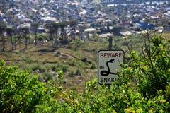 Guardi dal segnale stradale dei serpenti nei cespugli di Città del Capo, Sudafrica Fotografia Stock