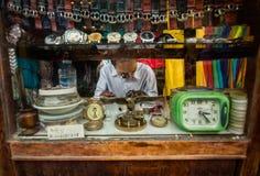 Guardi e pieghe dell'uomo della riparazione dell'orologio il suo commercio ad un supporto della via Immagini Stock Libere da Diritti