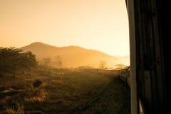 Guardi fuori il treno della finestra alla luce solare di mattina Immagine Stock