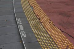 Guardi il vostro segno di punto sulle scale con la pavimentazione tattile Fotografia Stock Libera da Diritti