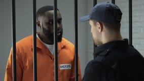 Guardia carceraria che dà la dose tossicodipendente nera del prigioniero maschio di polvere bianca archivi video