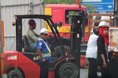 Guardia de seguridad en medio de trabajadores de construcción Foto de archivo libre de regalías