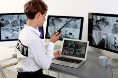 Guardia de seguridad femenino con el transmisor portátil que supervisa las cámaras caseras imagenes de archivo