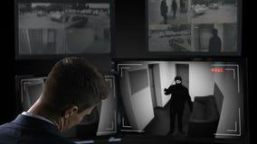Guardia de seguridad masculino que duerme delante de la cantidad del CCTV, freno del bandido en el edificio almacen de metraje de vídeo