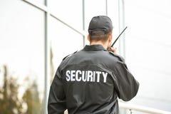 Guardia de seguridad masculino usando transmisor de la radio portátil fotografía de archivo