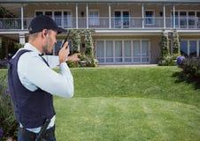 Guardia de seguridad que habla en radio mientras que señala en la casa fotos de archivo libres de regalías