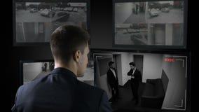 Guardia de seguridad que mira en cámaras de vigilancia corporativas, testigo de la escena del crimen metrajes