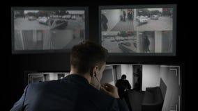 Guardia de seguridad que mira la cantidad del CCTV, llamando policía, rotura del ladrón en el edificio almacen de video