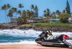 Guardia de vida Jet Ski en primero plano y persona que practica surf en fondo imagenes de archivo