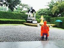 Guardia giurata che si siede e che porta impermeabile arancio per restare attento Fotografia Stock Libera da Diritti