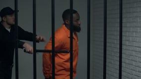 Guardia giurata della prigione che spinge prigioniero afroamericano, facendo uso della violenza, abuso archivi video