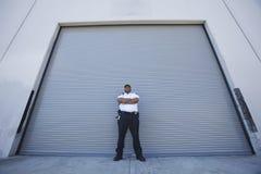 Guardia giurata Protects Warehouse Entrance Fotografie Stock Libere da Diritti