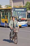 Guardia giurata sulla sua bici con il bus sui precedenti, Pechino, Cina Fotografia Stock