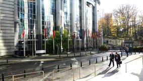 Guardia y turistas fuera del edificio del Parlamento Europeo con las banderas de diversas naciones almacen de video