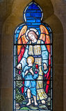 Guardian Angel with Child Stained Glass Window. Stained glass window showing a guardian angel watching over a child Royalty Free Stock Photos