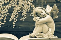 Guardian angel and spring flowers. On wooden background stock photo