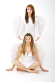 Guardian Angels. Two angels, one standing above the other with her hands poised on each side of the sitting angel's head Royalty Free Stock Photo