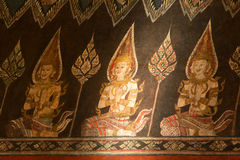 Guardian angles. Water color painting of guardian angles on wall in ancient temple in Bangkok in sunlight, Thailand Stock Images