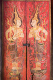 Guardian angles. Water color painting of guardian angles on wooden door in ancient temple in Bangkok, Thailand Stock Photography