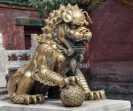 Guardian lion in the Forbidden city in Beijing in China. Animals protector. Lion plays with the ball. Red walls of pavilion stock photography