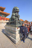 Guardian Lion in front of pavilion at Palace Museum, Beijing, China. BEIJING-OCT. 23, 2016. Visitors at guardian Lion in front of pavilion Palace Museum, listed Royalty Free Stock Image