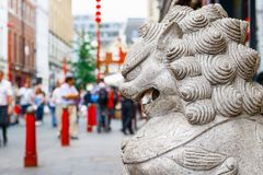 A guardian lion statue located in the crowded London Chinatown. A guardian lion statue with crowded London Chinatown in the background Royalty Free Stock Images