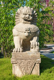 Guardian lion stone statue on pedestal in a park Stock Images