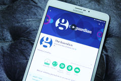 The Guardian mobile app. Downloading The Guardian mobile application from google play store on samsung tablet. The Guardian is a British daily newspaper, known stock image