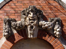 Guardian of the Realm. Ancient figure surrounded by fruit and vines, sometimes known as The Green Man used as a decorative flourish atop a doorway arch royalty free stock image