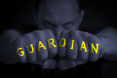 GUARDIAN written on an angry man's fists Royalty Free Stock Image