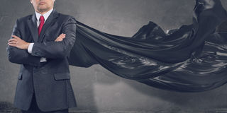 On guardiance of your interests . Mixed media. Aged businessman in black cape with arms crossed on chest. Mixed media Stock Images