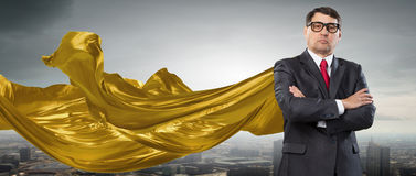 On guardiance of your interests . Mixed media. Aged businessman in golden cape with arms crossed on chest. Mixed media Royalty Free Stock Photos