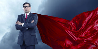 On guardiance of your interests . Mixed media. Aged businessman in red cape with arms crossed on chest. Mixed media Royalty Free Stock Photography