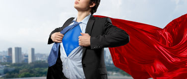 On guardiance of your interests. Mixed media . Mixed media. Young businessman in red cape tearing shirt on chest. Mixed media Royalty Free Stock Photos