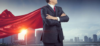 On guardiance of your interests . Mixed media. Senior businessman wearing cape with arms crossed on chest . Mixed media Stock Images