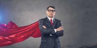 On guardiance of your interests . Mixed media. Senior businessman wearing cape with arms crossed on chest . Mixed media Royalty Free Stock Photos