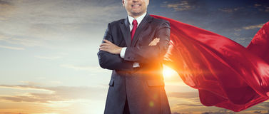 On guardiance of your interests . Mixed media. Senior businessman wearing cape with arms crossed on chest . Mixed media Stock Photo