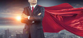 On guardiance of your interests . Mixed media. Senior businessman wearing cape with arms crossed on chest . Mixed media Royalty Free Stock Image
