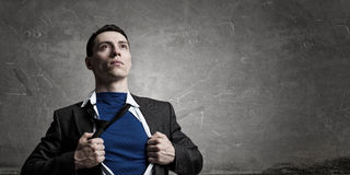 On guardiance of your interests. Mixed media. Young businessman acting like super hero tearing shirt on chest. Mixed media Royalty Free Stock Photo