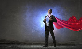 On guardiance of your interests. Mixed media. Young businessman in red cape tearing shirt on chest. Mixed media Royalty Free Stock Images