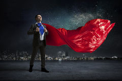 On guardiance of your interests. Mixed media. Young businessman in red cape tearing shirt on chest. Mixed media Stock Photos