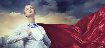 On guardiance of your interests . Mixed media. Young businesswoman dressed as superhero against cityscape background Royalty Free Stock Images