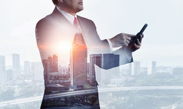 On guardiance of your interests. Senior businessman against modern cityscape using his smartphone Stock Photography