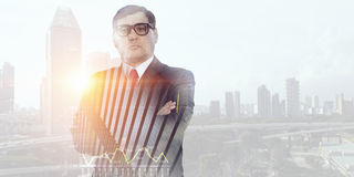On guardiance of your interests. Senior businessman with arms crossed on chest against modern cityscape Stock Image
