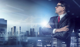 On guardiance of your interests. Senior businessman with arms crossed on chest against modern cityscape Royalty Free Stock Photography