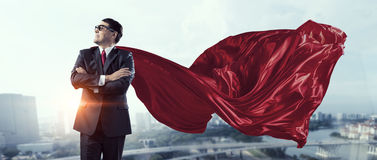 On guardiance of your interests. Senior businessman dressed as superhero against cityscape background Royalty Free Stock Images