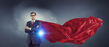 On guardiance of your interests. Senior businessman dressed as superhero against cloud background Royalty Free Stock Photos